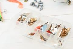Рыболовная удочка с вьюрком, приманками ложки, снастями и wobblers в коробке для улавливать или удить захватническую рыбу на бело Стоковое Изображение RF