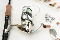 Рыболовная удочка с вьюрком, приманками ложки, снастями и wobblers в коробке для улавливать или удить захватническую рыбу на бело Стоковая Фотография RF