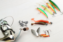 Рыболовная удочка с вьюрком, приманками ложки, снастями и wobblers в коробке для улавливать или удить захватническую рыбу на бело Стоковые Фотографии RF