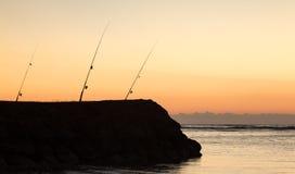 3 рыболовной удочки на заходе солнца над океаном Стоковые Изображения