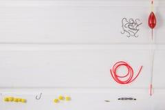 Рыболовные принадлежности на белой деревянной предпосылке Стоковая Фотография