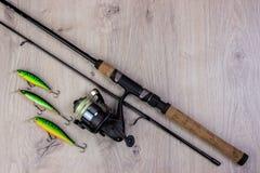 Рыболовные снасти - закручивать, крюки и прикормы рыбной ловли на светлой деревянной предпосылке стоковое фото rf