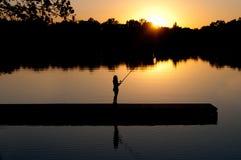 Рыболовство женщины на заходе солнца Стоковая Фотография