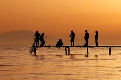 Рыболовство людей на заходе солнца Стоковая Фотография
