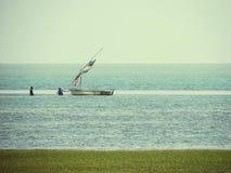 Рыболовы вытягивая традиционную рыбацкую лодку с побережья Мозамбика Стоковая Фотография