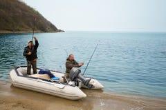 Рыболовы на море в штабелированных рыболовных удочках шлюпки стоковое фото rf