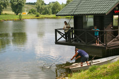 Рыболовы принимают вне рыб от воды Стоковое Изображение