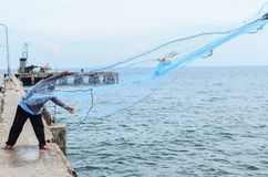 Рыболов бросая его сеть от шлюпки Стоковые Фотографии RF