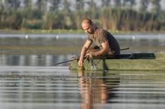 Рыболов вытягивает сеть стоковые фото