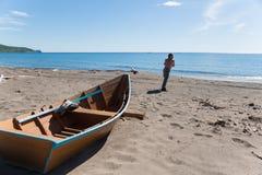 Рыболов вытягивает тяжелую деревянную шлюпку стоковое изображение rf