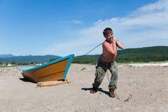 Рыболов вытягивает тяжелую деревянную шлюпку стоковые фотографии rf