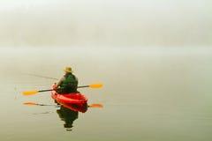 Рыболов в красном каяке Стоковые Фото