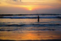 Рыболов в море на заходе солнца Стоковые Фото