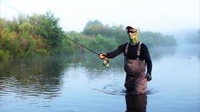 Рыболов идет рыбная ловля мухы в реке утра сток-видео