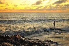 Рыболов и пляж захода солнца Стоковая Фотография RF