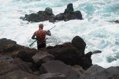 Рыболов копья остроги на скалистом береге Стоковое Изображение RF