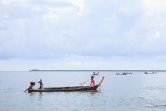 Рыболов на деревянных медузах задвижки шлюпки в море Стоковые Изображения RF