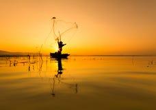 Рыболов на деревянных рыбах задвижки силуэта шлюпки на озере в утре Стоковые Фотографии RF