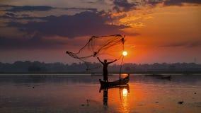 Рыболов на деревянных рыбах задвижки силуэта шлюпки на озере в утре Стоковое фото RF