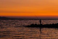Рыболов на предпосылке заходящего солнца Стоковое Изображение RF