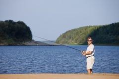 Рыболов на речном береге Стоковые Фото