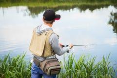 Рыболов на речном береге Стоковые Изображения RF