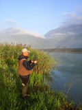 Рыболов на речном береге Стоковое Изображение