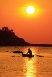 Рыболов на шлюпке над драматическим заходом солнца Стоковая Фотография RF