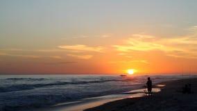 Рыболов пляжа на заходе солнца видеоматериал