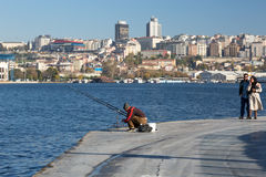 Рыболов сидя на прогулке набережной и романтичном идти пар Стоковые Изображения RF