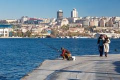 Рыболов сидя на прогулке набережной и романтичном идти пар Стоковое фото RF