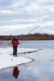 Рыболов стоя на реке с рыболовной удочкой стоковое фото