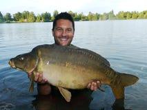 Рыболов с его карпом зеркала Стоковая Фотография RF