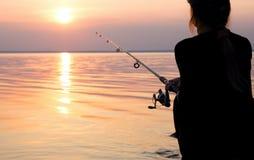 Рыбы девушки на речном береге Стоковые Изображения