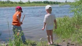 2 рыбы задвижки детей на речном береге Красивейший ландшафт лета воссоздание обеда напольное сток-видео