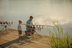 Рыбы задвижки сына помощи папы с рыболовной удочкой Стоковая Фотография RF
