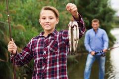 Рыбы задвижки показа мальчика Fisher Стоковые Фотографии RF