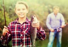 Рыбы задвижки показа мальчика Fisher Стоковая Фотография RF