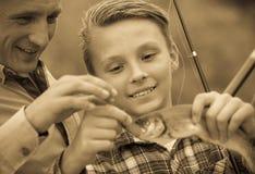 Рыбы задвижки удерживания мальчика подростка на крюке Стоковое фото RF
