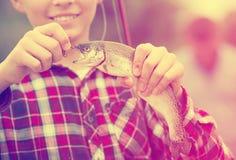 Рыбы задвижки удерживания мальчика подростка на крюке Стоковые Изображения