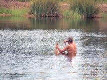 Рыбы звероловства рыболова в перемете реки сельской местности Стоковые Изображения