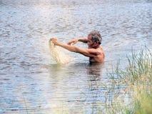 Рыбы звероловства рыболова в перемете реки сельской местности Стоковое Изображение