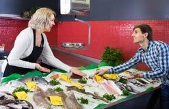 Рыбы клиента покупая в магазине Стоковые Фотографии RF