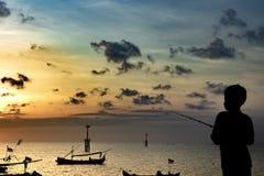 Рыбы мальчика на пристани в деревенском порте Силуэт мальчика на заходе солнца, держа удя поляка и смотря заходящее солнце стоковые изображения