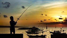Рыбы мальчика на пристани в деревенском порте Силуэт мальчика на заходе солнца, держа удя поляка и смотря заходящее солнце стоковые фотографии rf