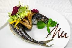 Рыбы моря, одетые с овощами и оливками на белой плите Рыбы моря, одетые с овощами и оливками на белой плите Hori Стоковые Фото