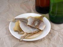 Рыбы на белых плите и пивной бутылке Стоковое Изображение RF