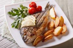 Рыбы Dorado с зажаренными картошками и крупным планом лимона горизонтально Стоковая Фотография