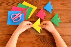 Рыбы Origami красочные, бумажные листы, ножницы Ребенок держит бумажный лист в его руках и делать рыб origami Стоковое Фото