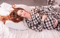 Рыжеволосая беременная женщина лежит в уютной кровати стоковое фото